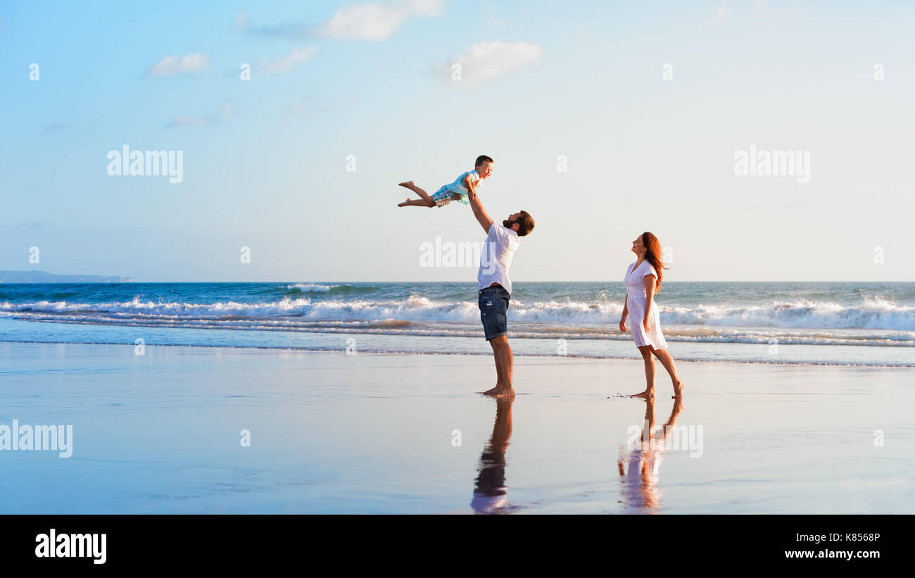 Happy family holidays. Joyful father, mother, baby son walk with fun along edge of sunset sea surf on black sand beach. Active parents and children. - Stock Image
