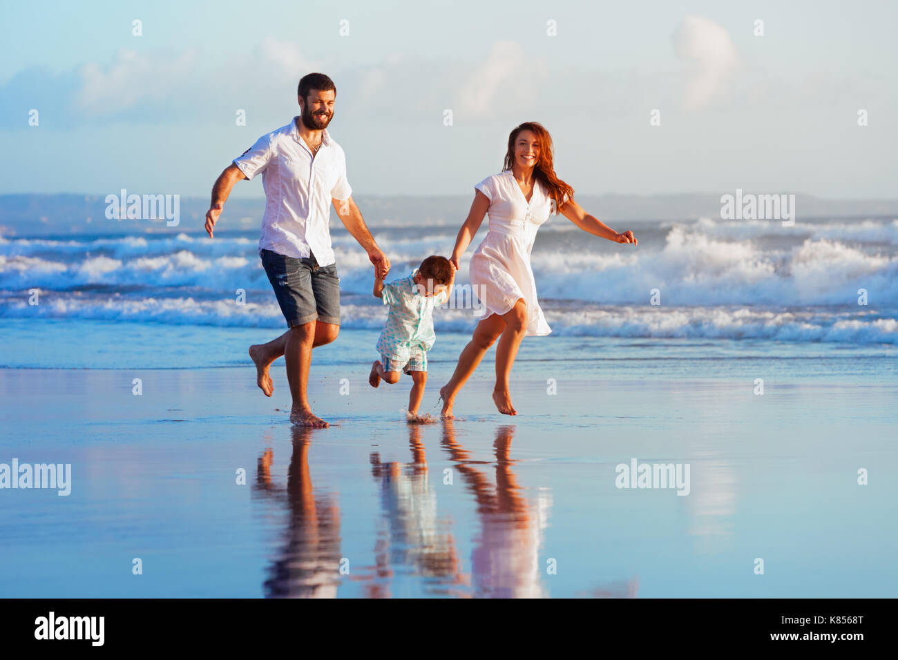 Happy family - father, mother, baby son have fun together, child run with splashes by water pool along sunset sea surf on black sand beach. - Stock Image