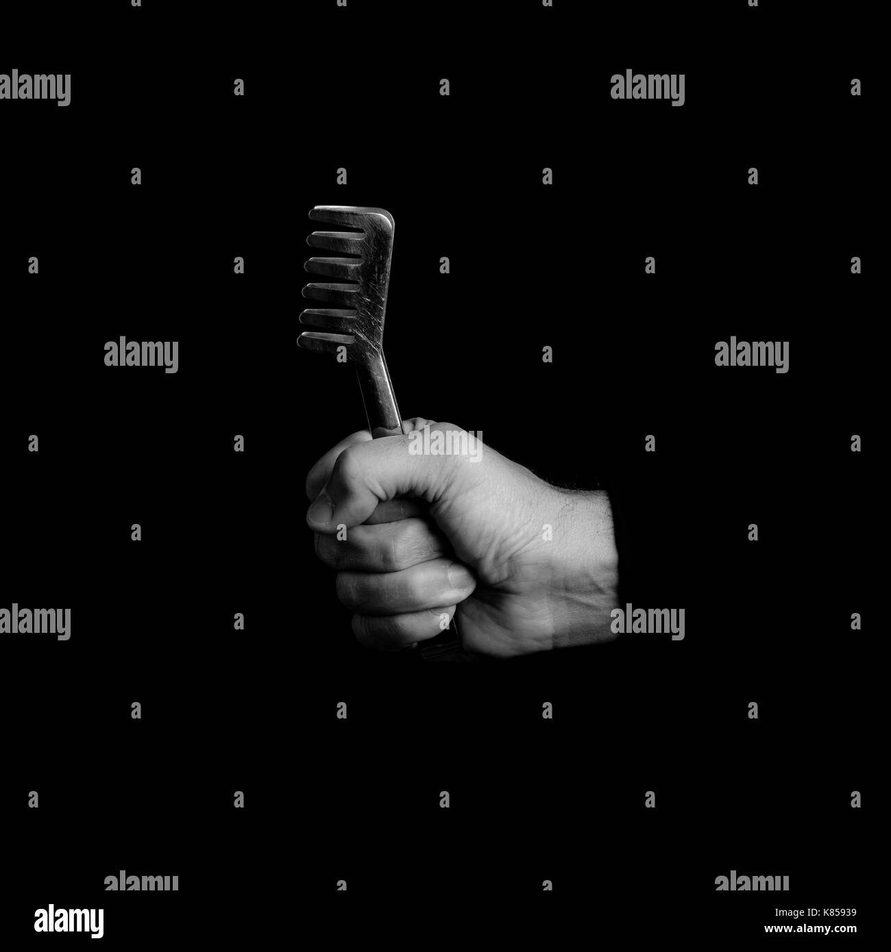 pasta pincer - kitchen tools in a man's hand - black and white photo - Stock Image