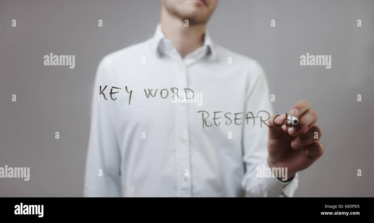 Keyword research , Man Writing on Glass - Stock Image