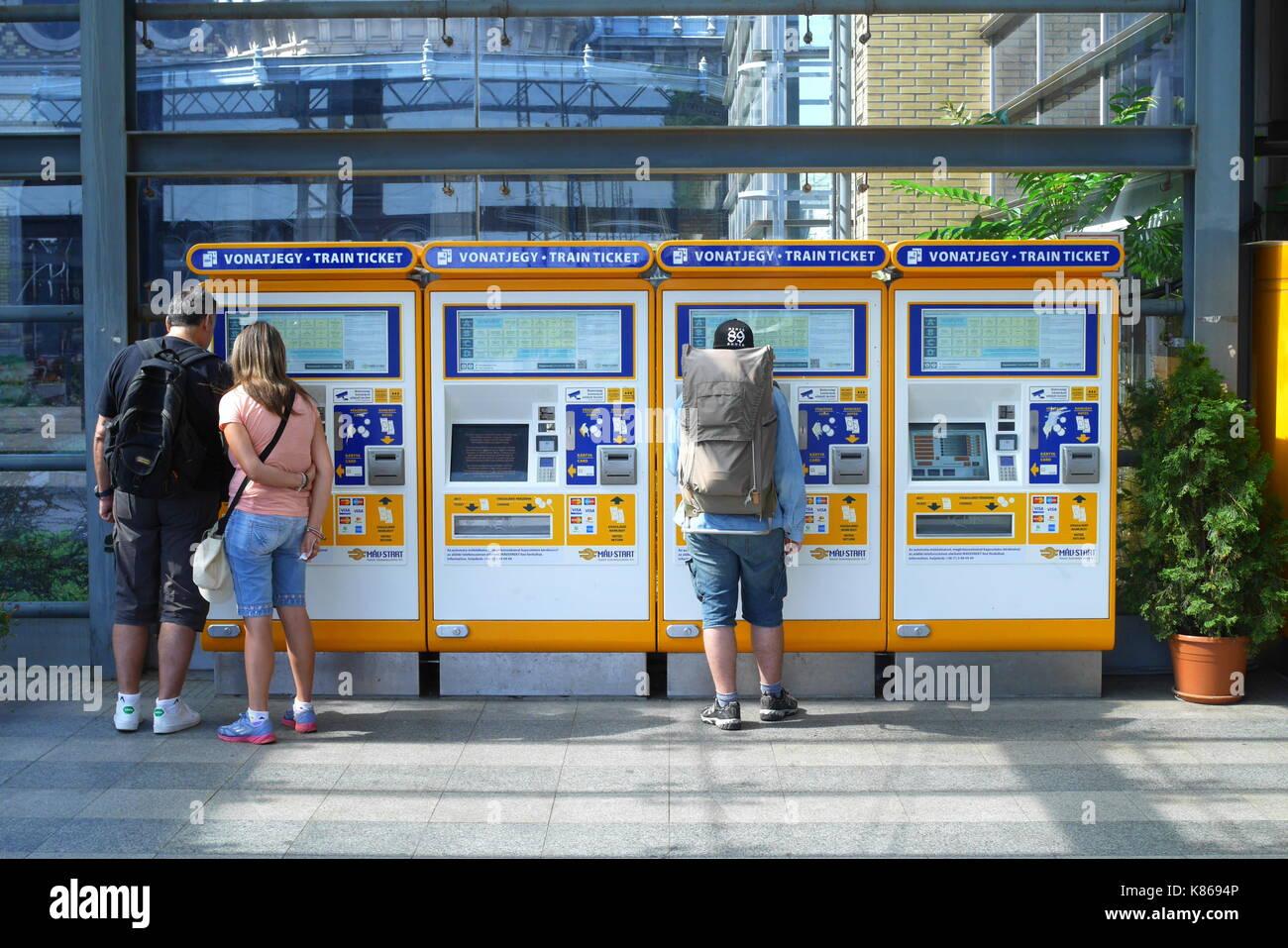 Passengers buying train tickets from self-service ticket machines, Nyugati Palyaudvar, Budapest, Hungary Stock Photo