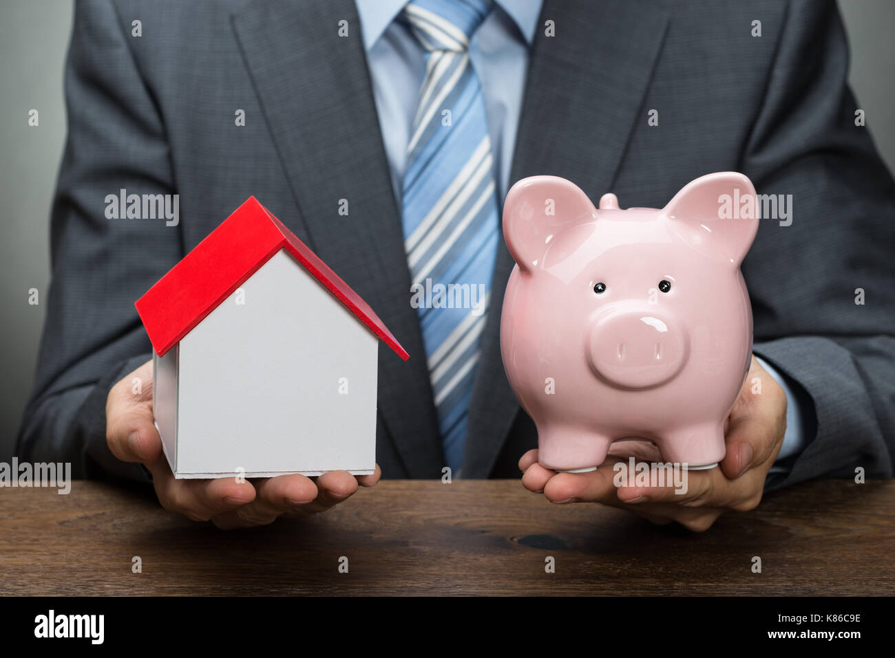 Businessperson Hands Holding A Piggy Bank And House Model At Desk - Stock Image