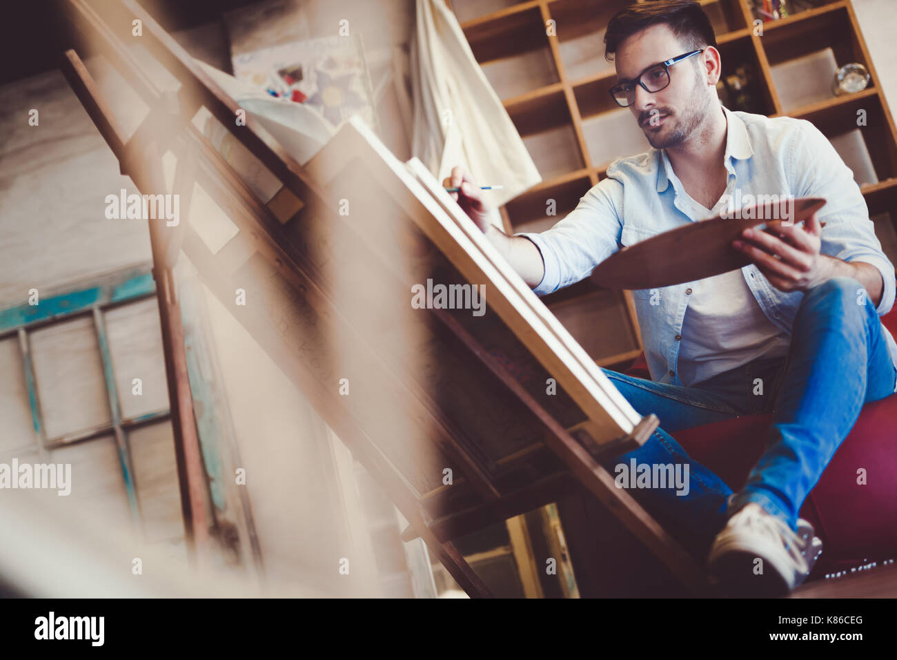 Male art school artist painting with oil on canvas - Stock Image