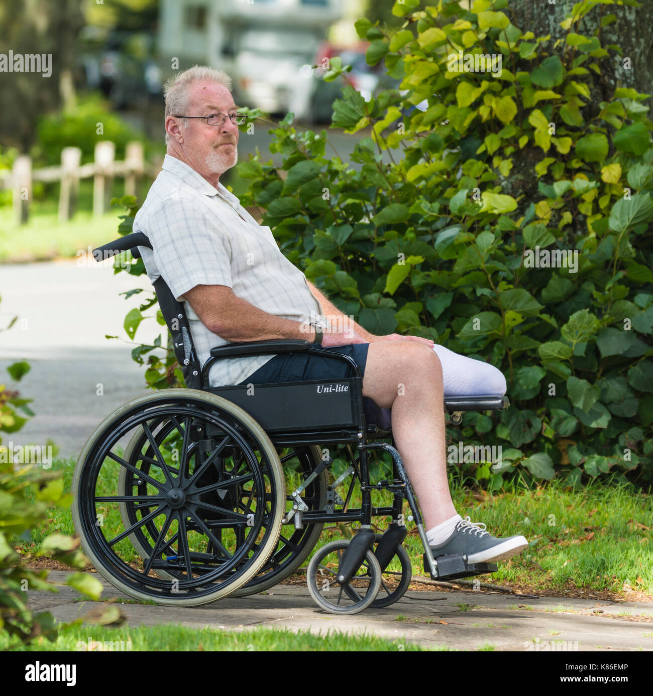 Middle aged man with an amputated leg in a wheelchair. - Stock Image