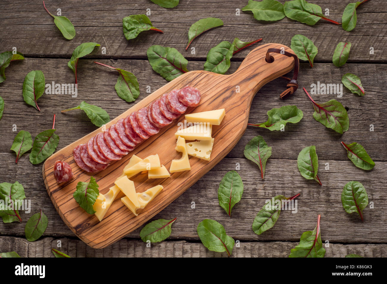 cheese and salami on kitchen board on rustic background. Top view with copy space and herbs . - Stock Image