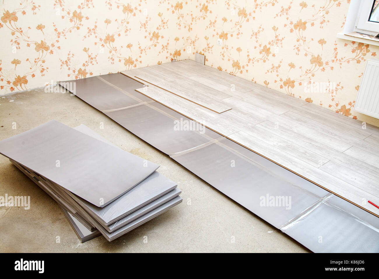 laminate boards prepared for laying on the floor in the room closeup - Stock Image