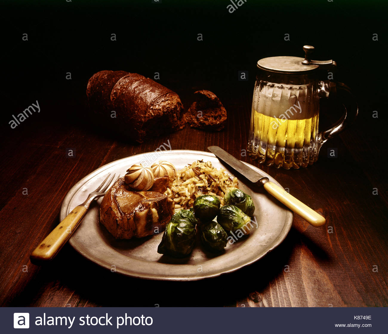TABLE SETTING WITH LAMB CHOP, BRUSSELS SPROUTS & WILD RICE ON A PEWTER PLATE. BONE HANDLE KNIFE AND FORK, BEER, AND PUMPERNICKEL ON WOODEN TABLE. - Stock Image