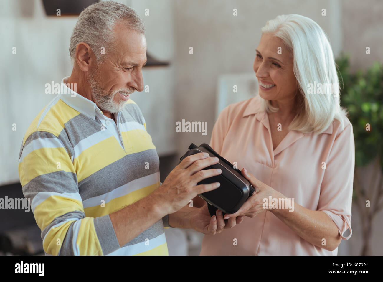 Waist up of a positive retired couple holdign virtual reality glasses - Stock Image