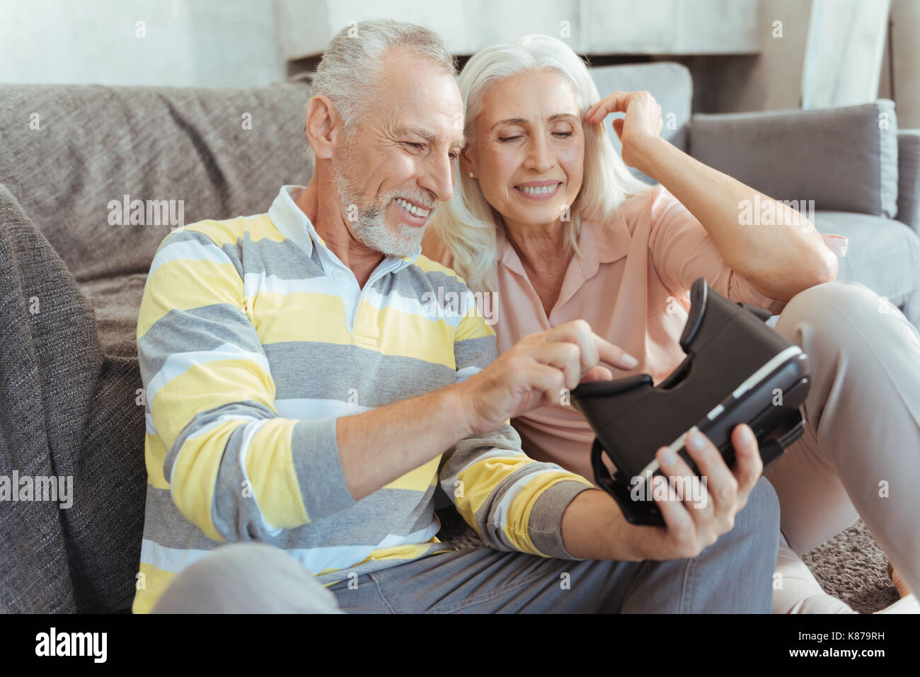 Positive aged couple trying up virtual reality device - Stock Image