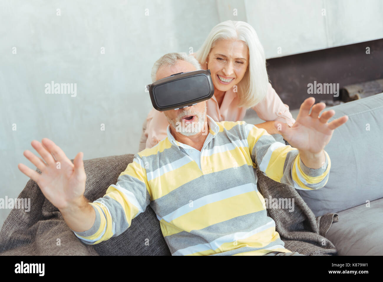 Surprised aged man wearing VR glasses - Stock Image