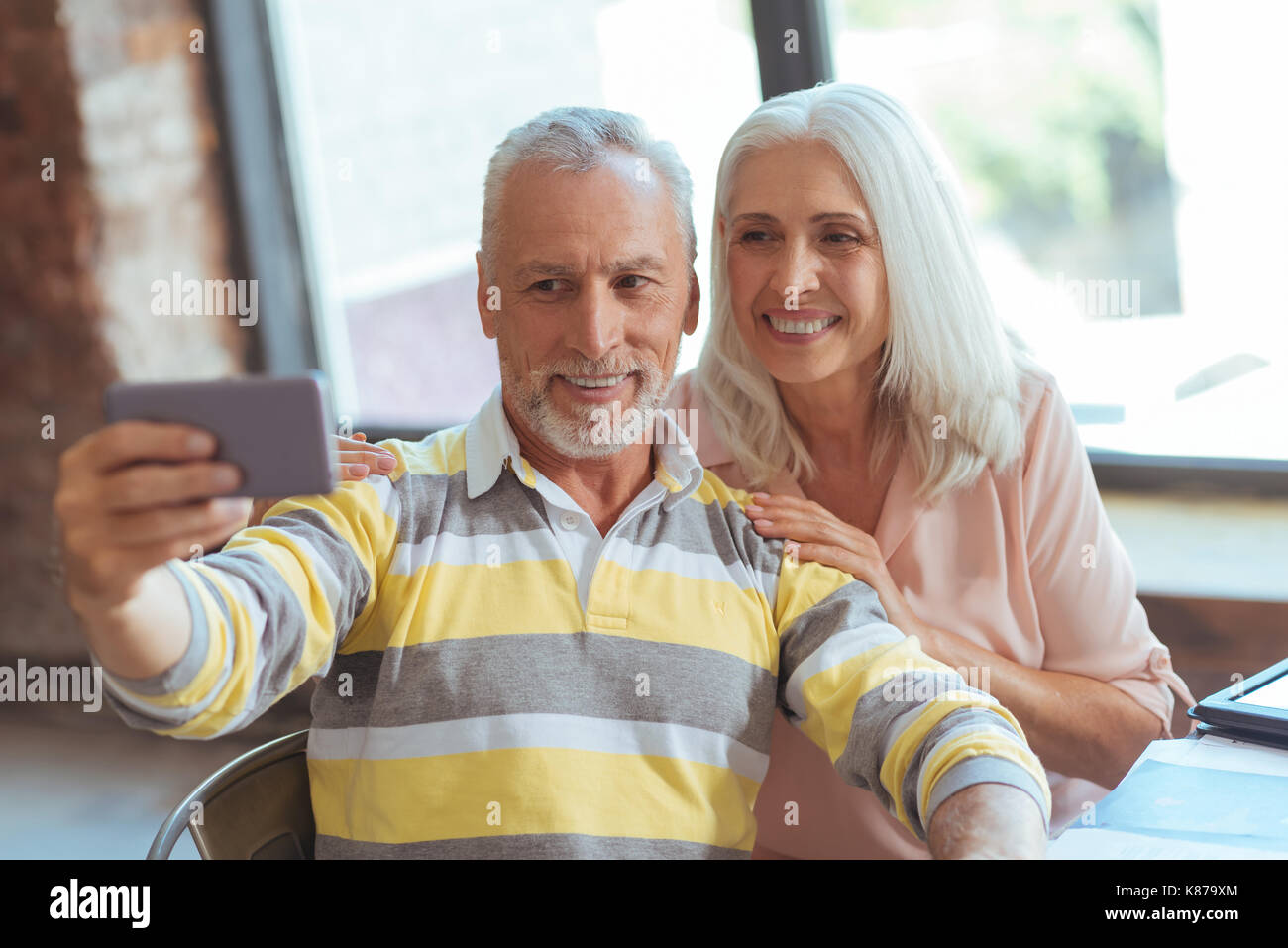 Positive aged couple making selfies - Stock Image