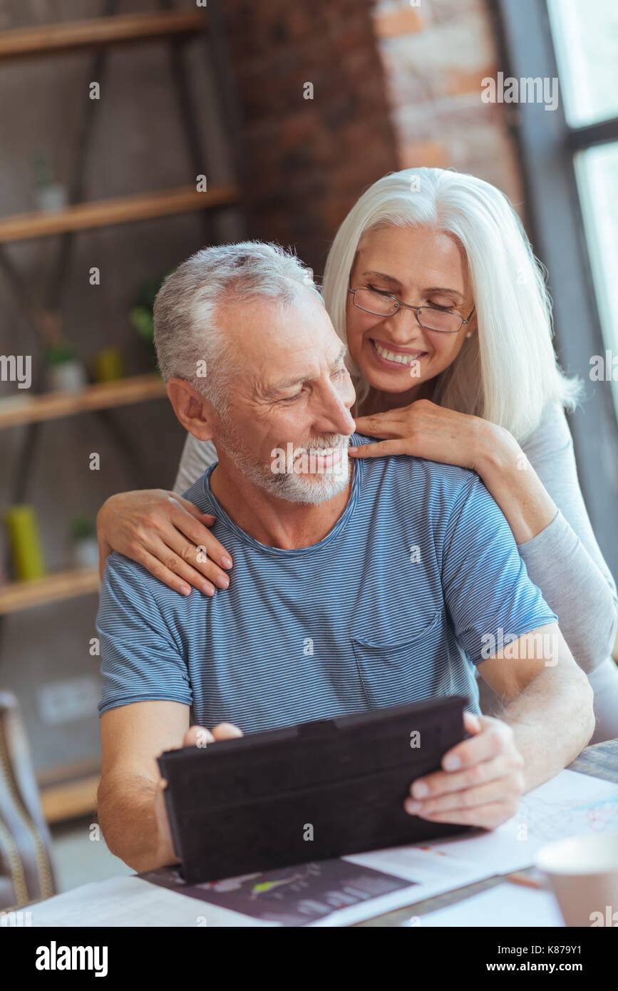 Loving aged couple using tablet at home - Stock Image