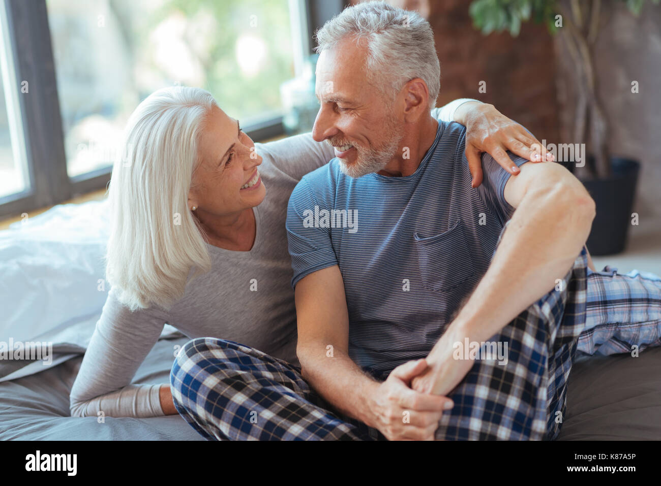 Cheerful nice aged couple resting in the bedroom - Stock Image