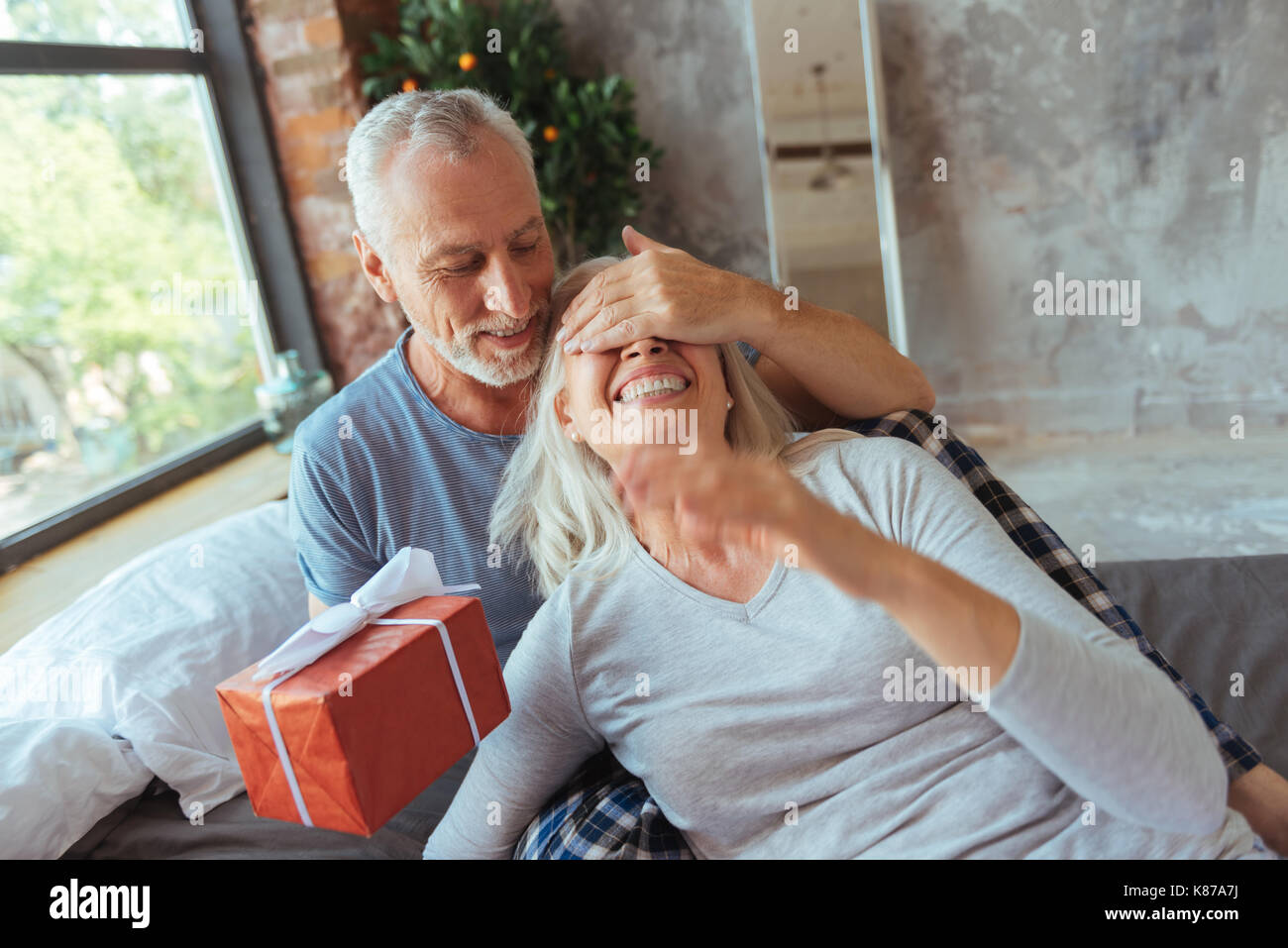 Loving aged man making a present for his wife - Stock Image