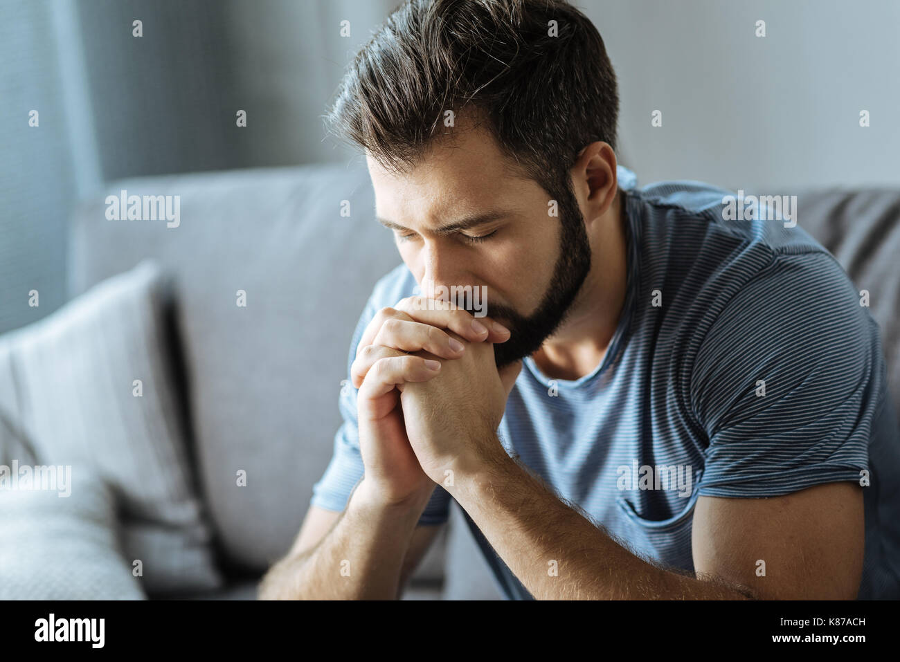 Unhappy young man holding his chin - Stock Image