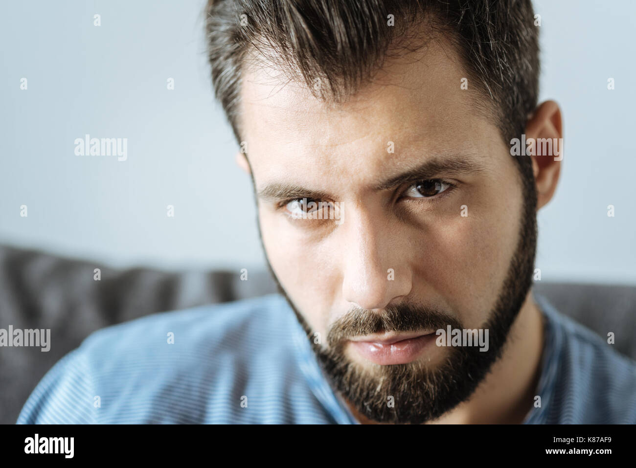 Portrait of a cheerless handsome man looking at you - Stock Image