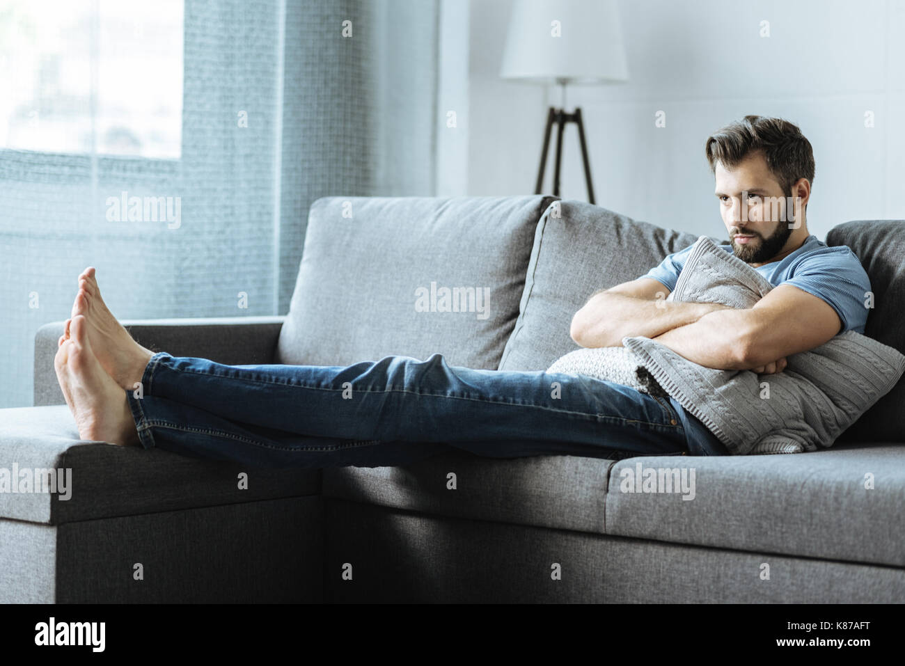Unhappy depressed man holding a cushion - Stock Image