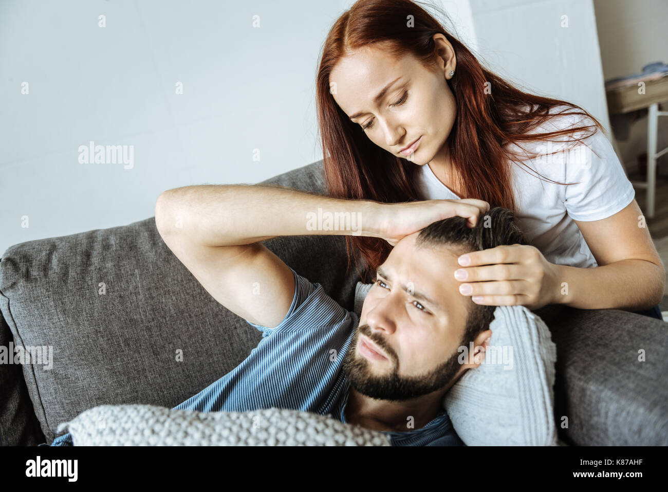 Nice unhappy woman looking at her boyfriend - Stock Image