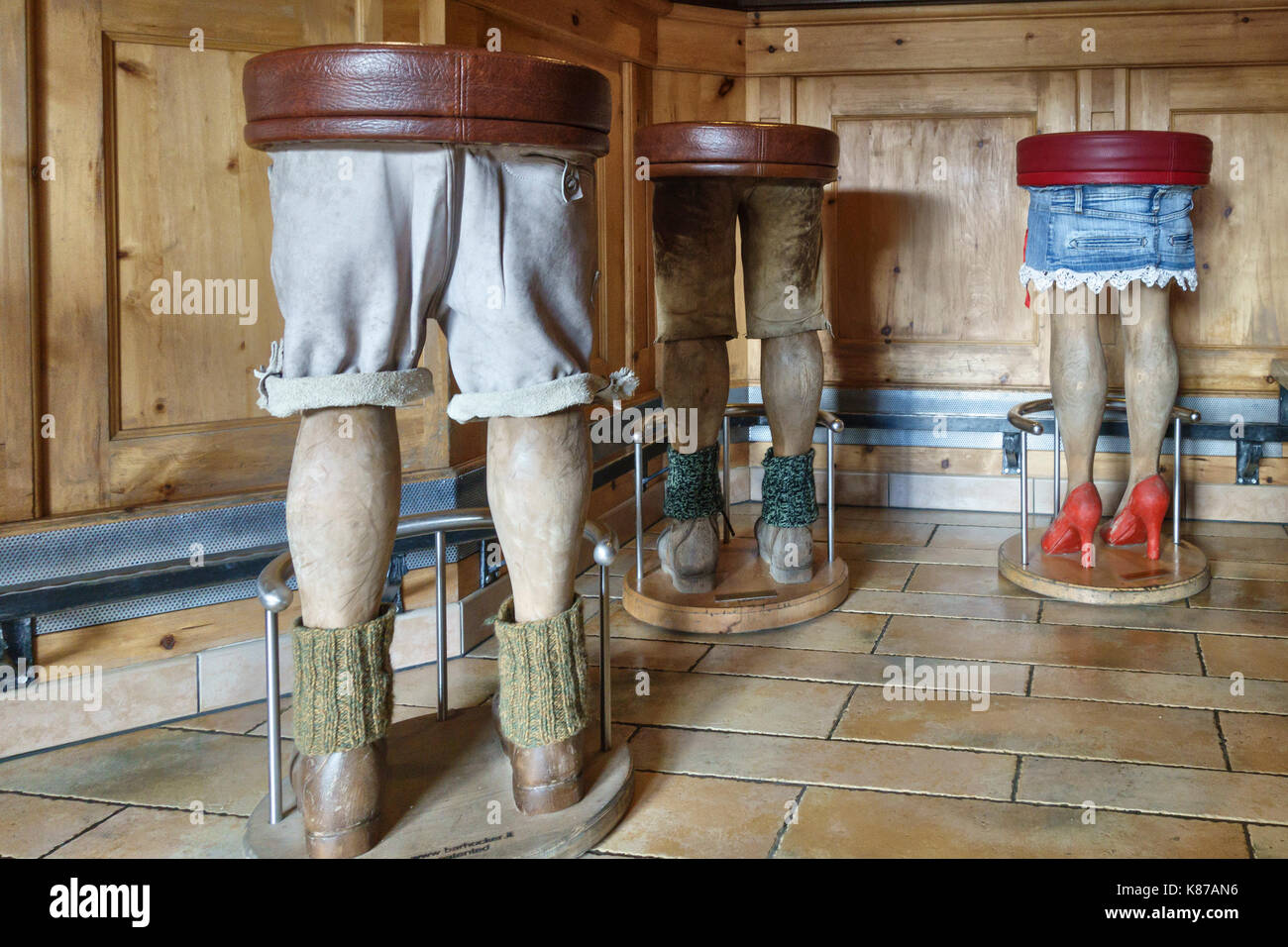 The Dolomites, Northern Italy. Unusual bar stools shaped like hikers' legs in the mountain guesthouse Rifugio Sennes Stock Photo