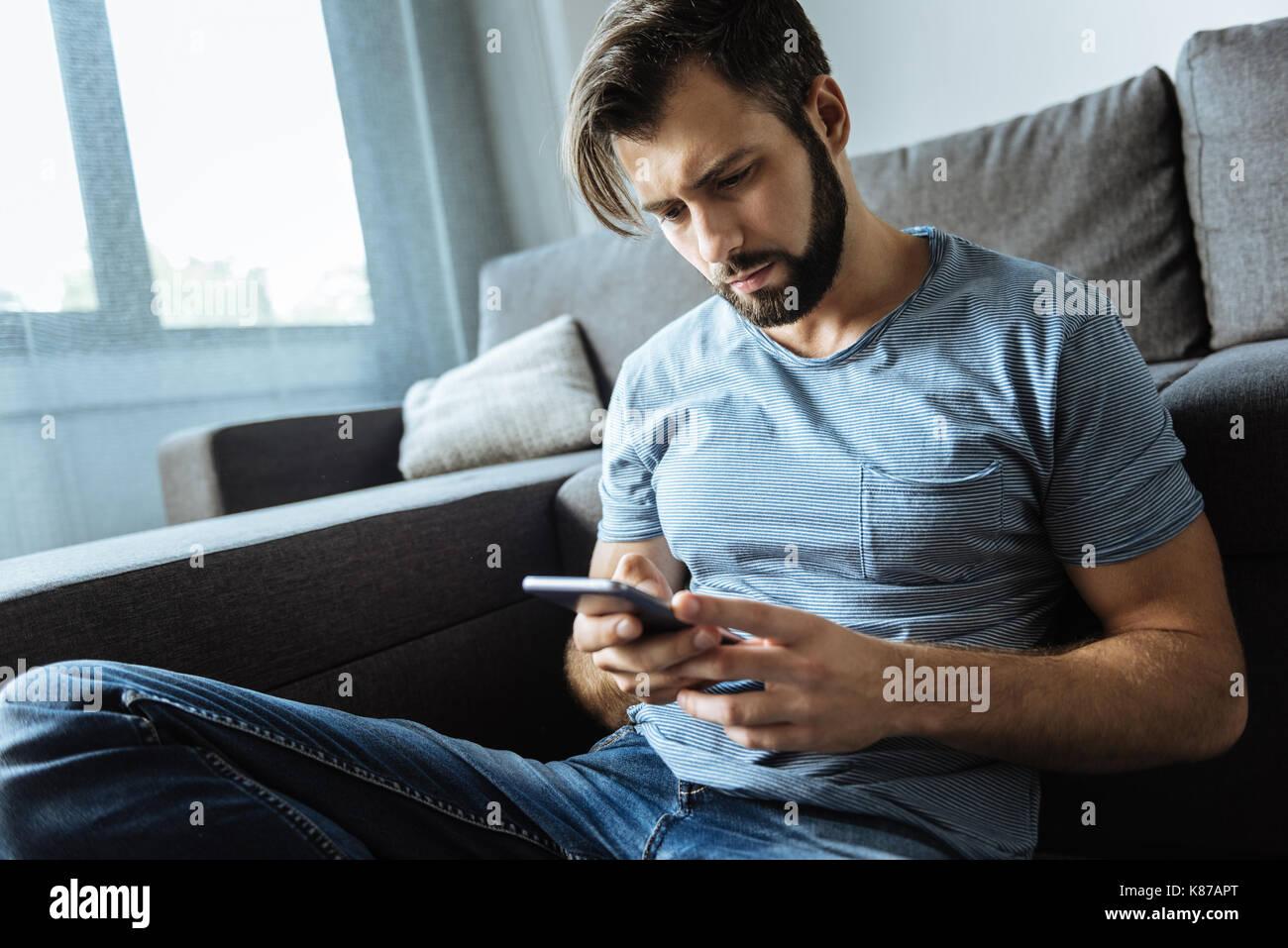 Unhappy sad man using his smartphone Stock Photo