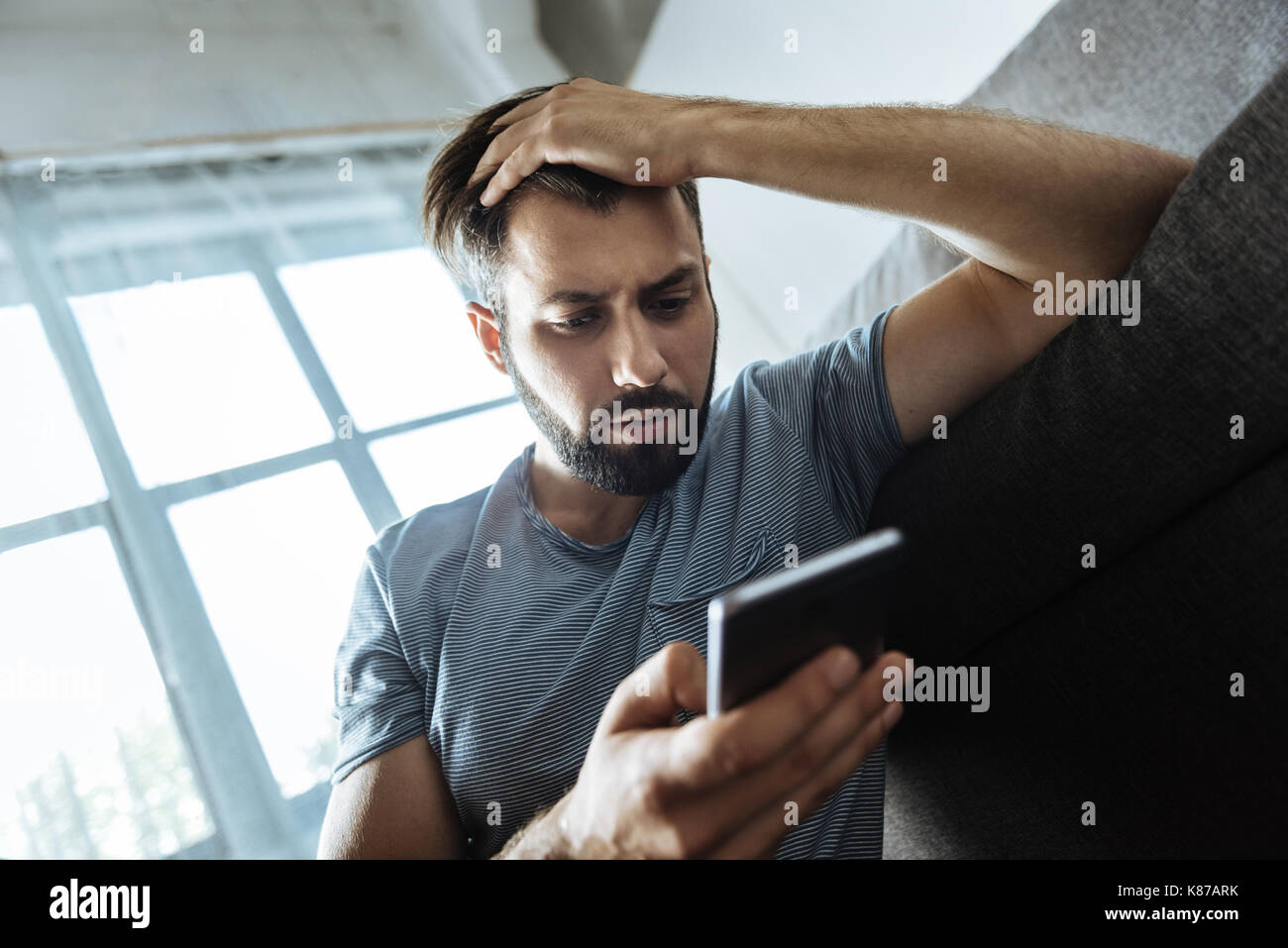 Gloomy unhappy man suffering from depression - Stock Image