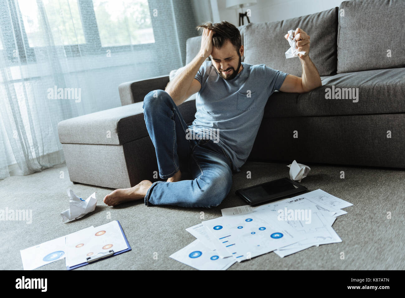 Unhappy stressed out man working at home - Stock Image
