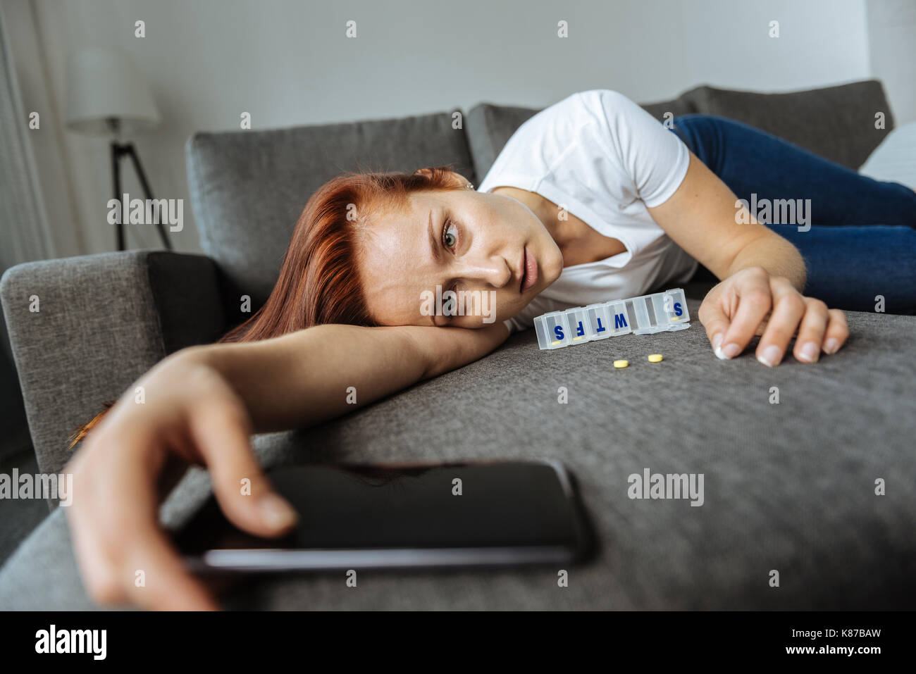 Sad exhausted woman holding her smartphone - Stock Image