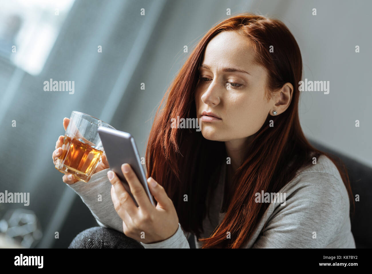 Pleasant sad woman holding a glass of whisky - Stock Image