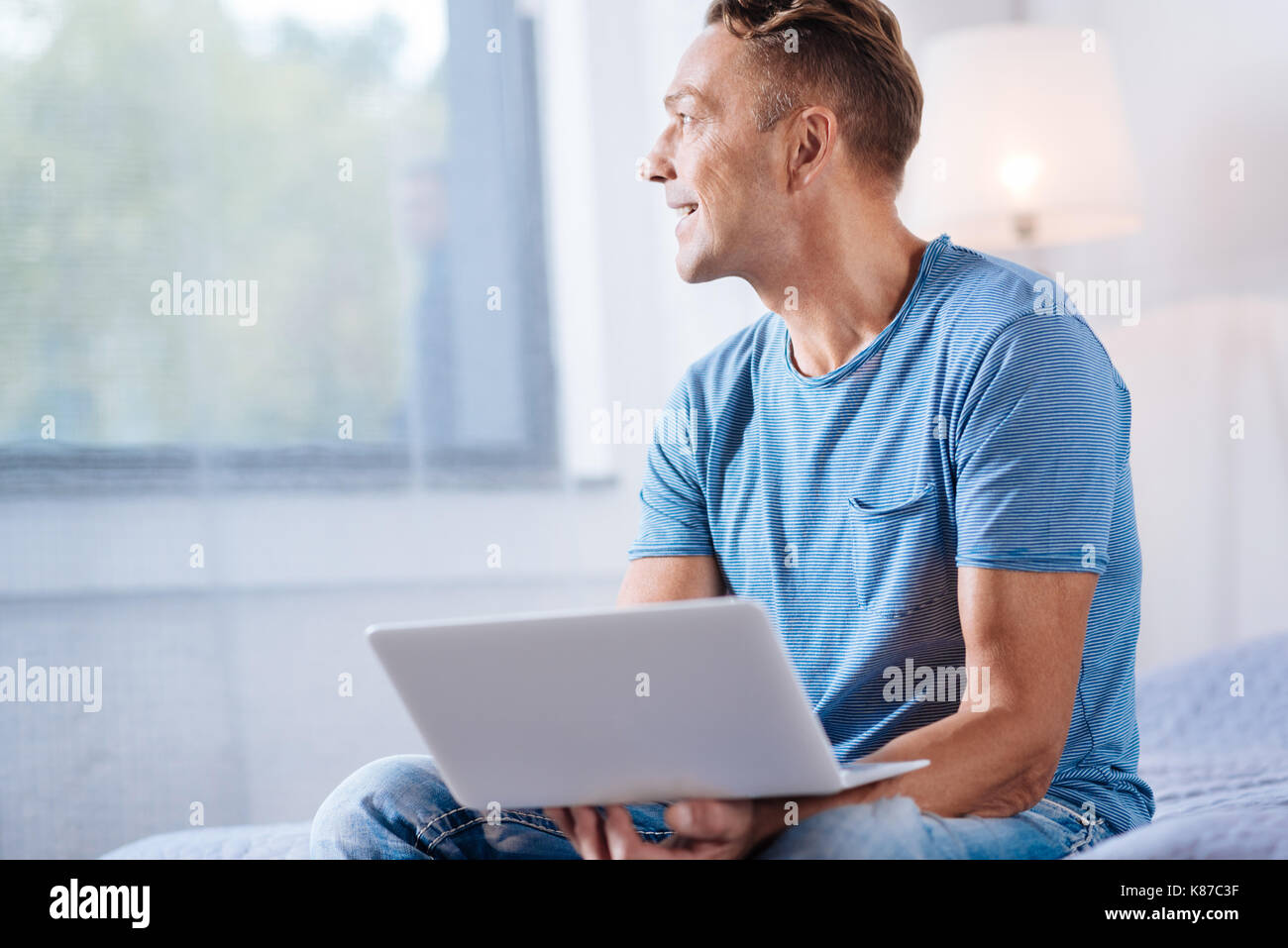 Cheerful man holding laptop and looking into the window - Stock Image