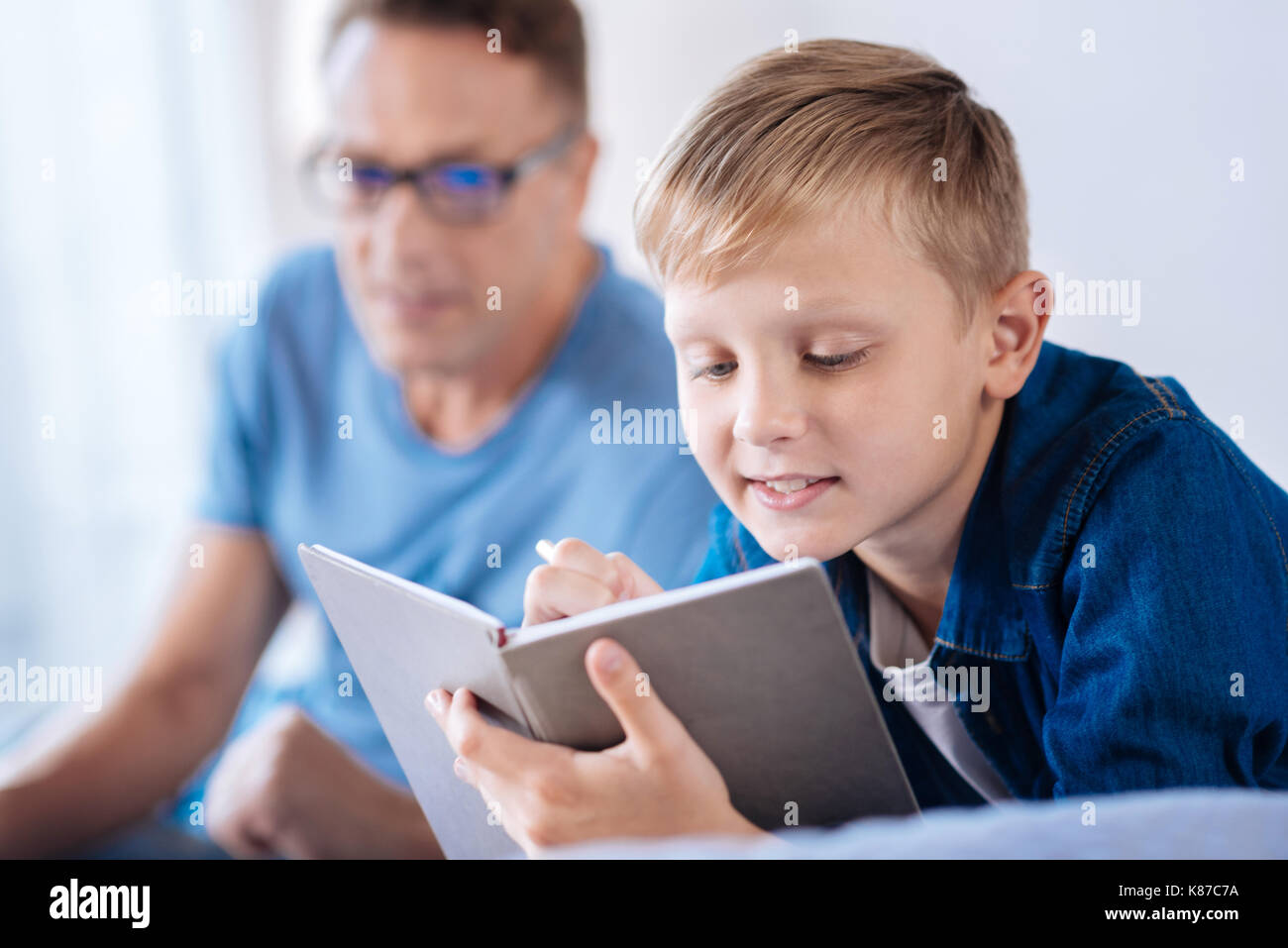 Cute pre-teen boy writing poems in his diary - Stock Image