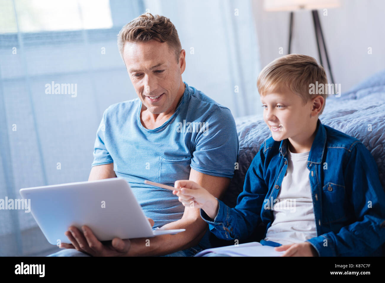 Cute pre-teen boy discussing presentation with his father - Stock Image