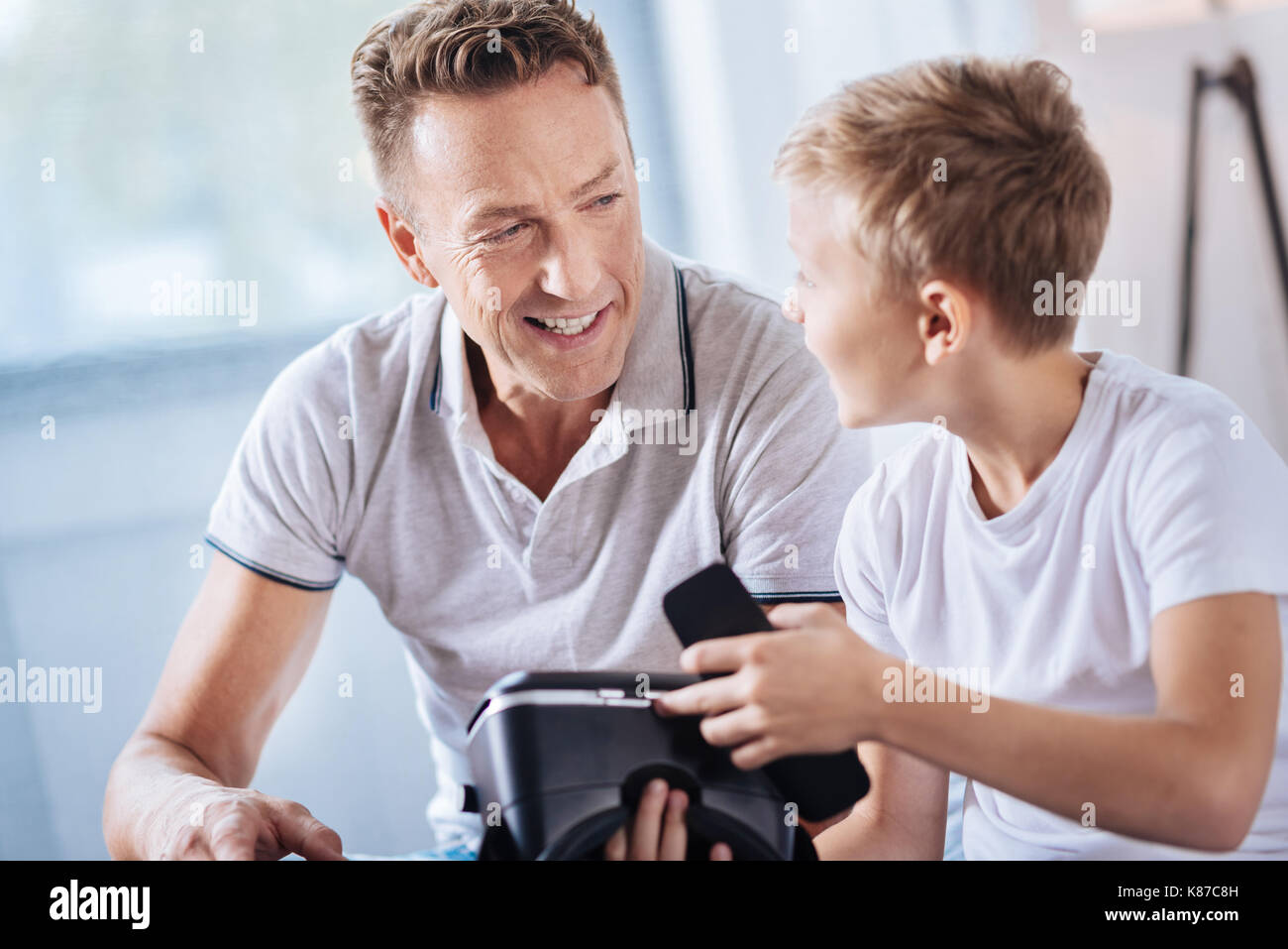 Pre-teen boy asking father how to open VR headset - Stock Image