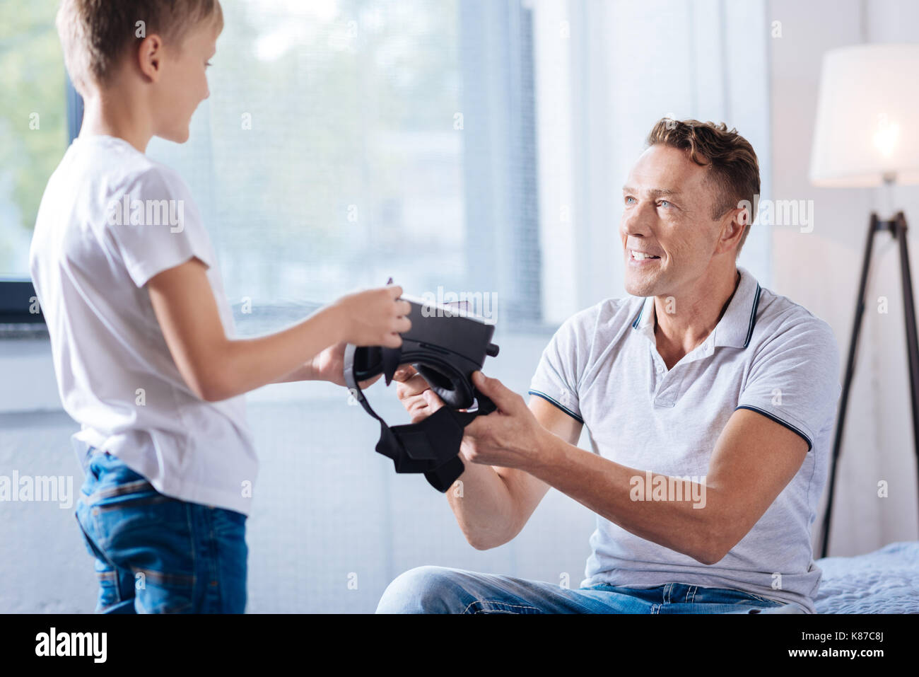 Pre-teen boy giving his father a VR headset - Stock Image