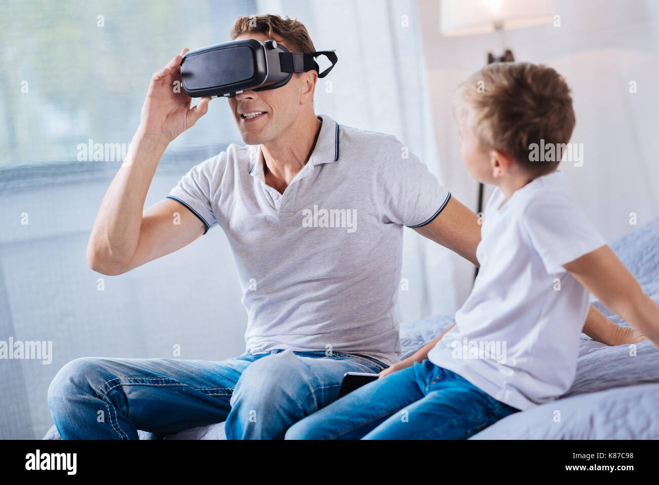 Pre-teen son watching his father test VR headset - Stock Image