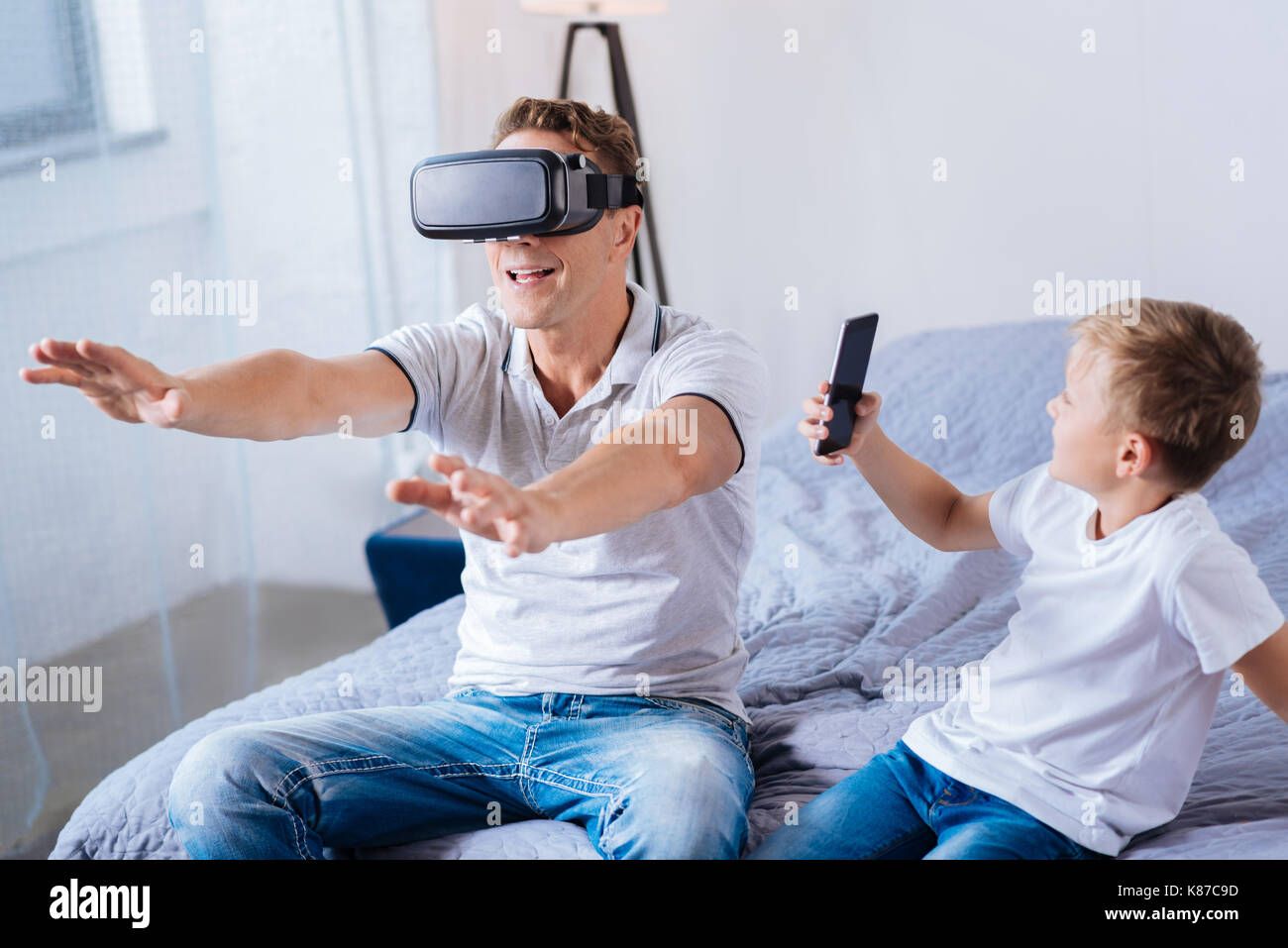 Cheerful boy filming his father testing VR headset - Stock Image