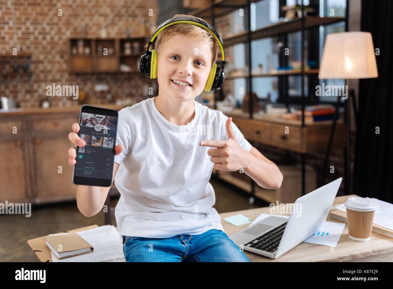 Smiling boy showing his favorite music streaming app - Stock Image