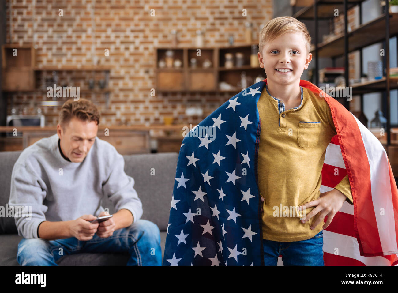 Pleasant pre-teen boy posing with US flag - Stock Image