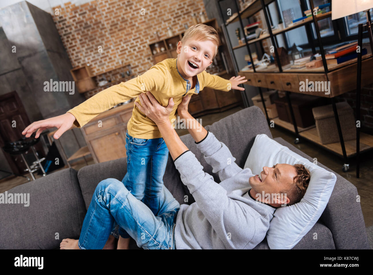 Joyful boy playing with his father on sofa - Stock Image