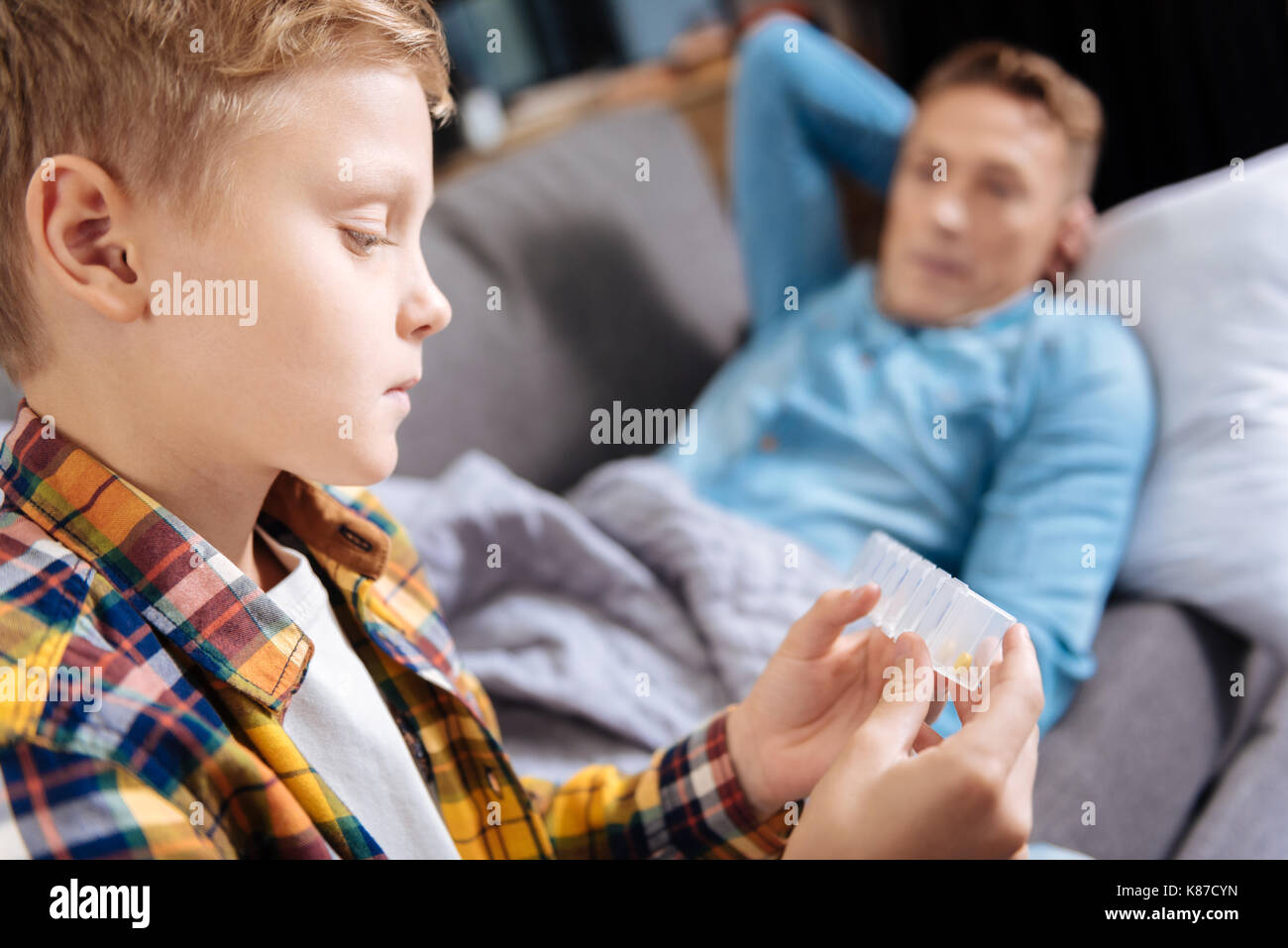 Close up of pre-teen boy holding pill organizer - Stock Image