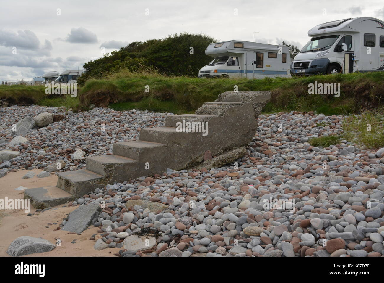 Concrete formed steps stairs on sandy pebble beach coastal erosion poor maintenance motorhome campervans camp site at Rosemarkie in Scotland - Stock Image