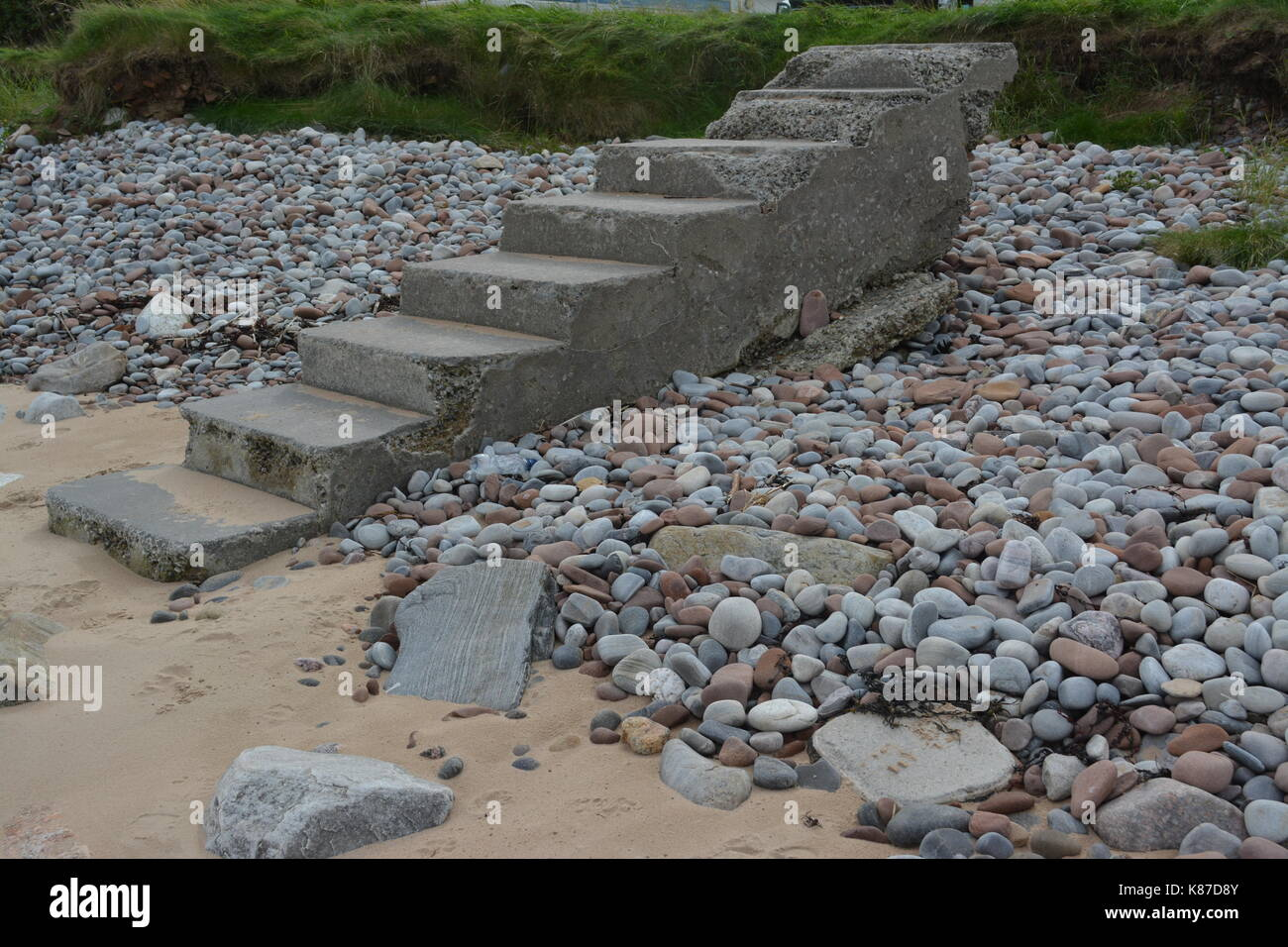 Concrete formed steps stairs on sandy pebble beach leading no where due to coastal erosion poor maintenance at Rosemarkie in Scotland - Stock Image