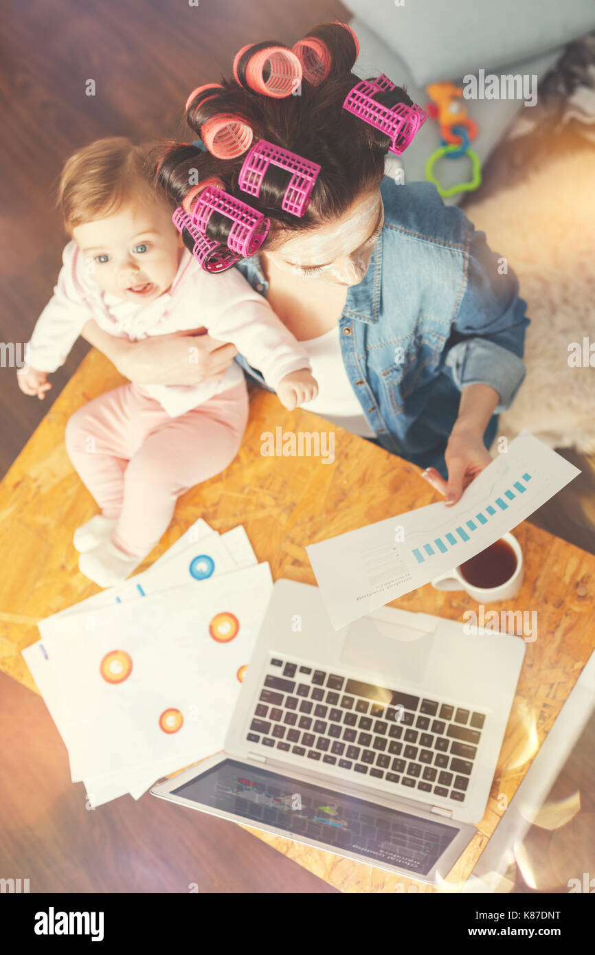 Top view photo of single mother while working at home - Stock Image