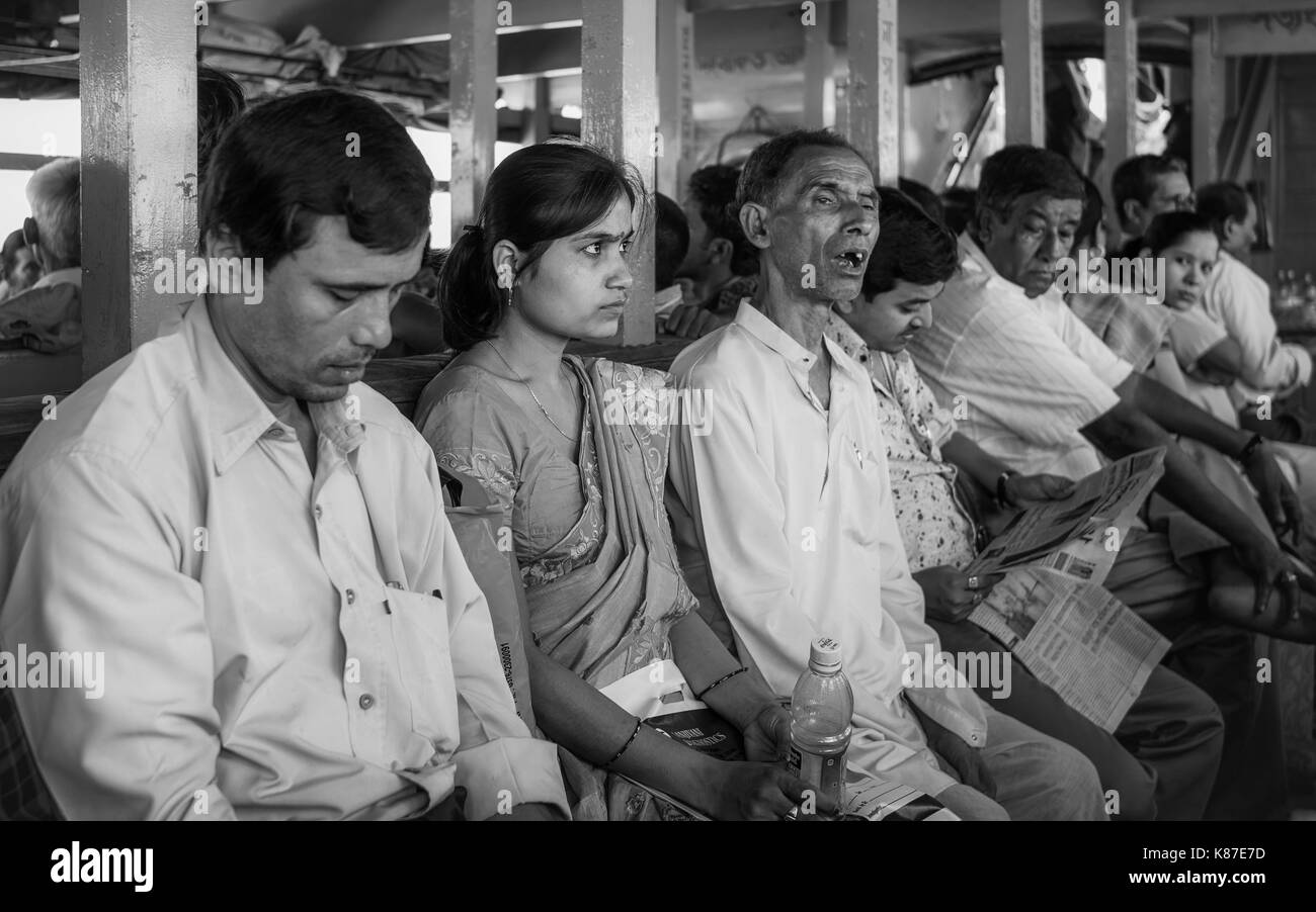 Passengers on board aging wooden ferry cross mighty Brahmaputra river during monsoon near Majuli, Assam, India. - Stock Image