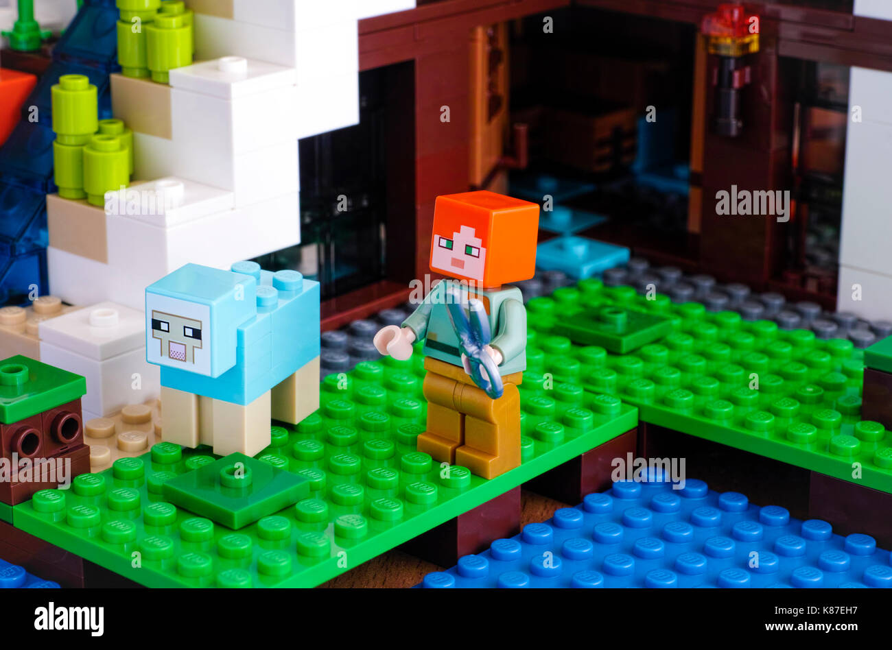 Tambov, Russian Federation - June 25, 2017 Lego Minecraft. Alex with sheep shears catching to shear the dyed sheep on Waterfall Base. Studio shot. - Stock Image