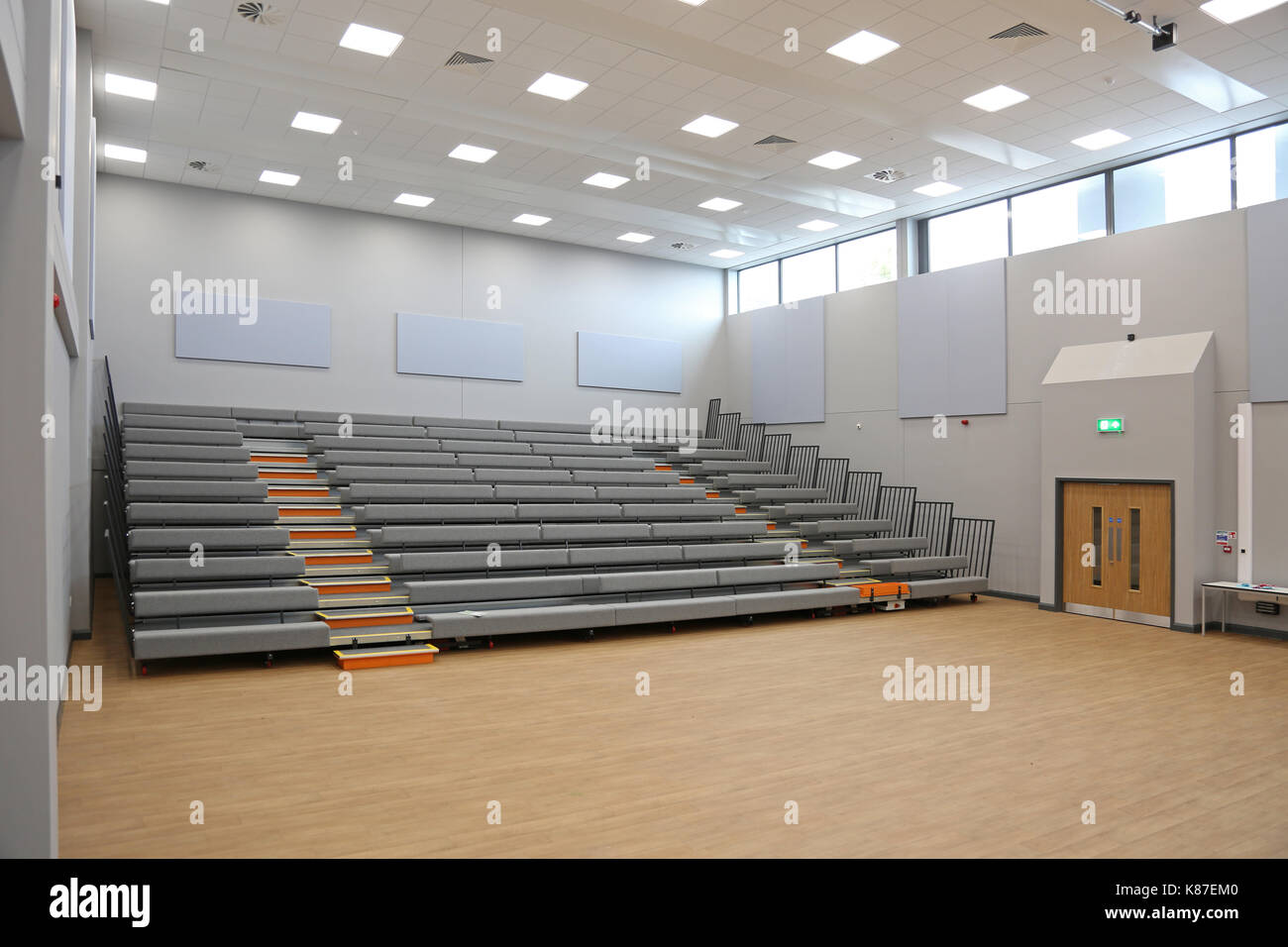 Interior of an assembly hall at a new London academy school. Shows retractable 'bleacher' seating in position for use. - Stock Image