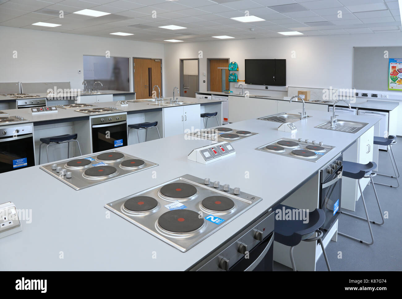 Domestic Science / cookery classroom in a new, London secondary school. Shows hobs and ovens and teachers bench beyond. - Stock Image