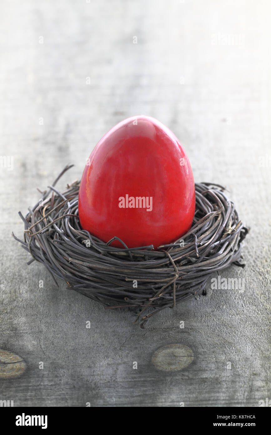 Red Easter egg in the nest - Stock Image