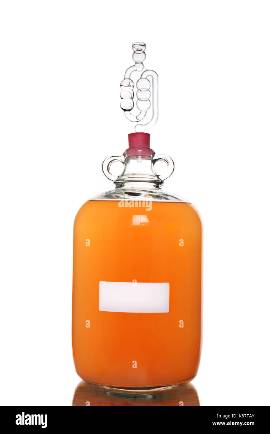 Peach wine fermenting in a demijohn, isolated on a white background. Stock Photo