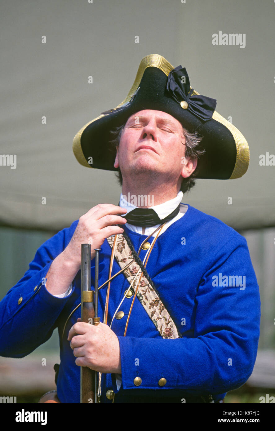 A man with a muzle loading rifle dressed in a Revolutionary War French Army uniform and wearing a tricorn hat. - Stock Image