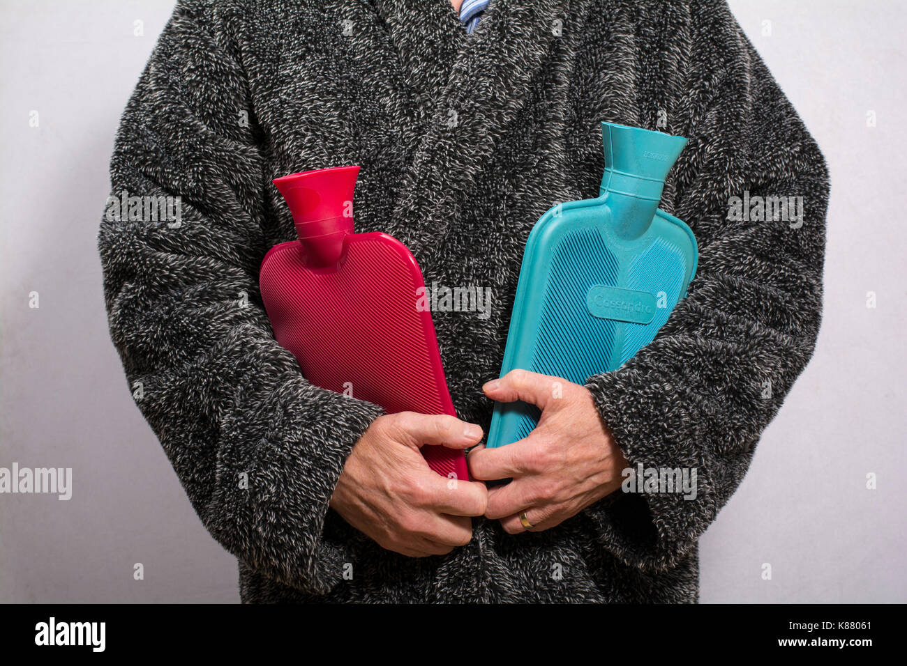 Man in a fluffy dressing gown holding two hot water bottles - Stock Image